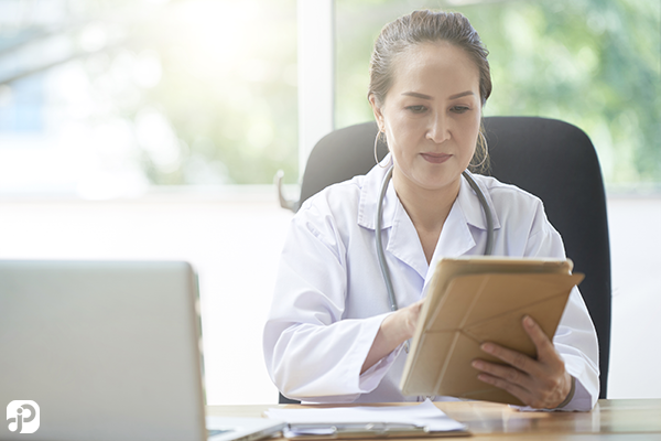 healthcare administrator working with her technology that was just password authenticated by her managed service provider. staying within HIPAA compliance and avoiding fines.